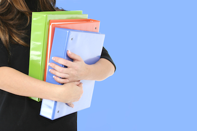 Mid section view of a businesswoman carrying notebooks