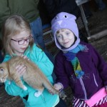 A blonde girl wearing a teal fleece coat holds an orange cat at a farm. Her sister stands next to her with a purple kitty hat on her head. She is also wearing a purple fleece coat. Around her waist, she carries both her epinephrine auto injectors in a bright-pink SpiBelt around her waist so they are close in case of a life-threatening reaction.