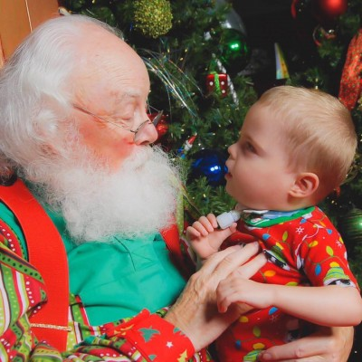 young boy with trach visiting with Santa