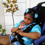 young girl sitting in purple adapted stroller
