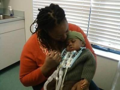 mother holding baby with trach