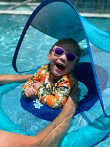 young child swimming in a float