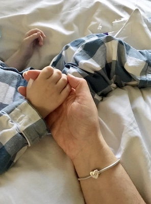 mother holding son's hand