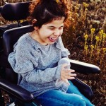 child laughing in wheelchair