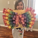 child holding butterfly craft